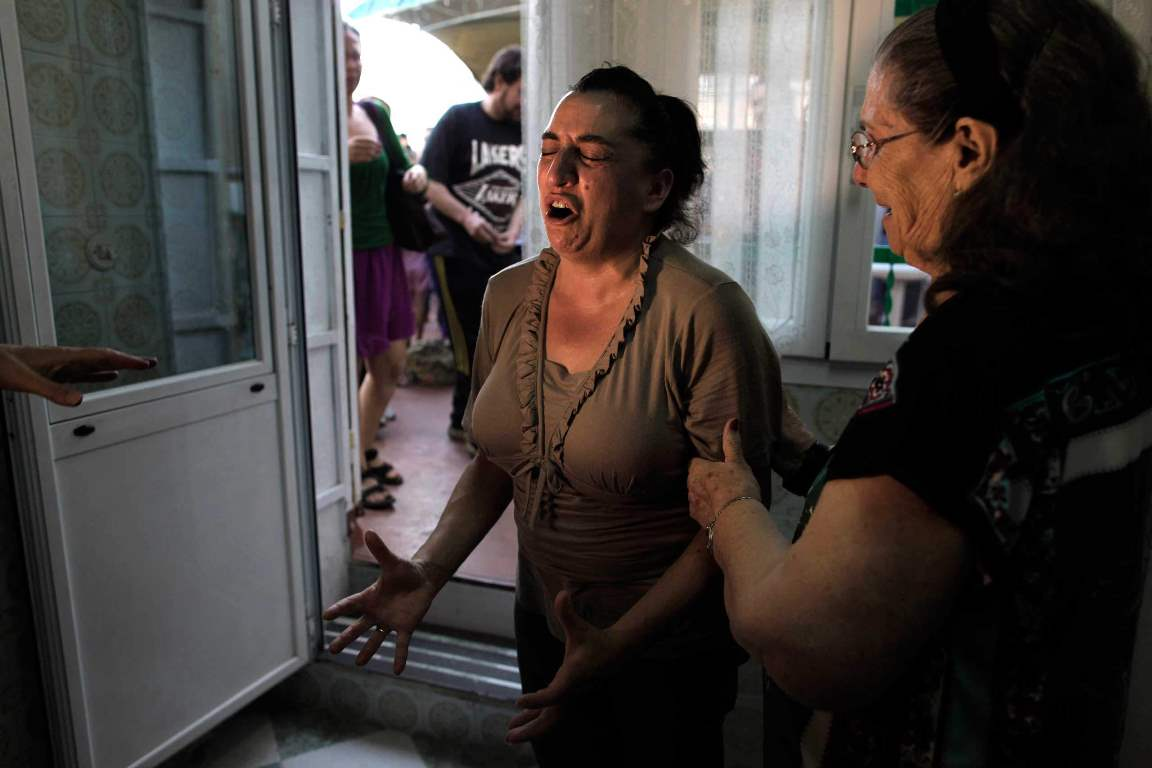 Luisa Gracia Gonzalez, 44 years old, centre, cries as her family eviction and the demolition of her house by a forced expropriation was postponed in Madrid, Spain, Wednesday, Aug. 14, 2013. The Government of Madrid applies a forced expropriation on Luisa Gracia Gonzalez and her family members including two couples with two children each and two elderly people. Her sister Angeles Gracia Gonzalez says the Government of Madrid tries to expropriate of their house since 2004 (during the Spanish property bubble) to build apartments and sell them as what she considers a real estate speculation with the excuse that the house interferes with the Urban Plan. She says the government offers them 326.000 euros ($ 432.377) approximately half of what the family received as appraisal for the house, euros 742.000 ($984.097). The eviction and demolition was not carried out due to the opposition of the Victims' Mortgage Platform (PAH). (AP Photo/Andres Kudacki)
