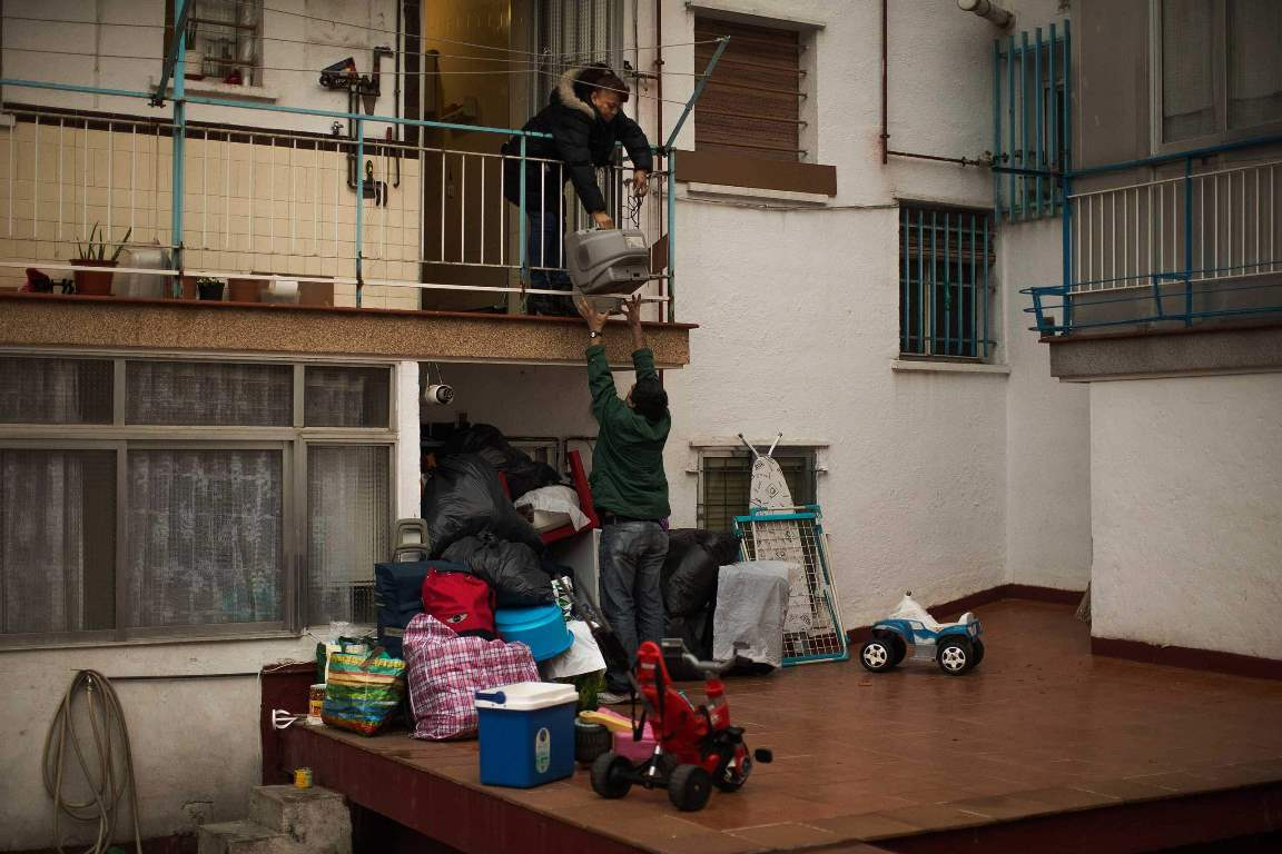 Mercedes Pincay, 50 years, empties her apartment through the back door as riot police surround them to evict her and her partner in Madrid, Spain, Monday, Dec. 15, 2014. The landlord's loss of the apartment to a Bankia bank caused Mercedes Pincay and her partner Aristides Apolo's eviction. Mercedes Pincay lived with Apolo, 58 years, unemployed, in a foreclosed apartment that was owned by her sister who stopped paying her mortgage fees. Mercedes and Apolo stayed occupying the apartment as they could not afford to pay rent due to their financial situation and she was recovering from breast cancer. The eviction was carried out. (AP Photo/Andres Kudacki)