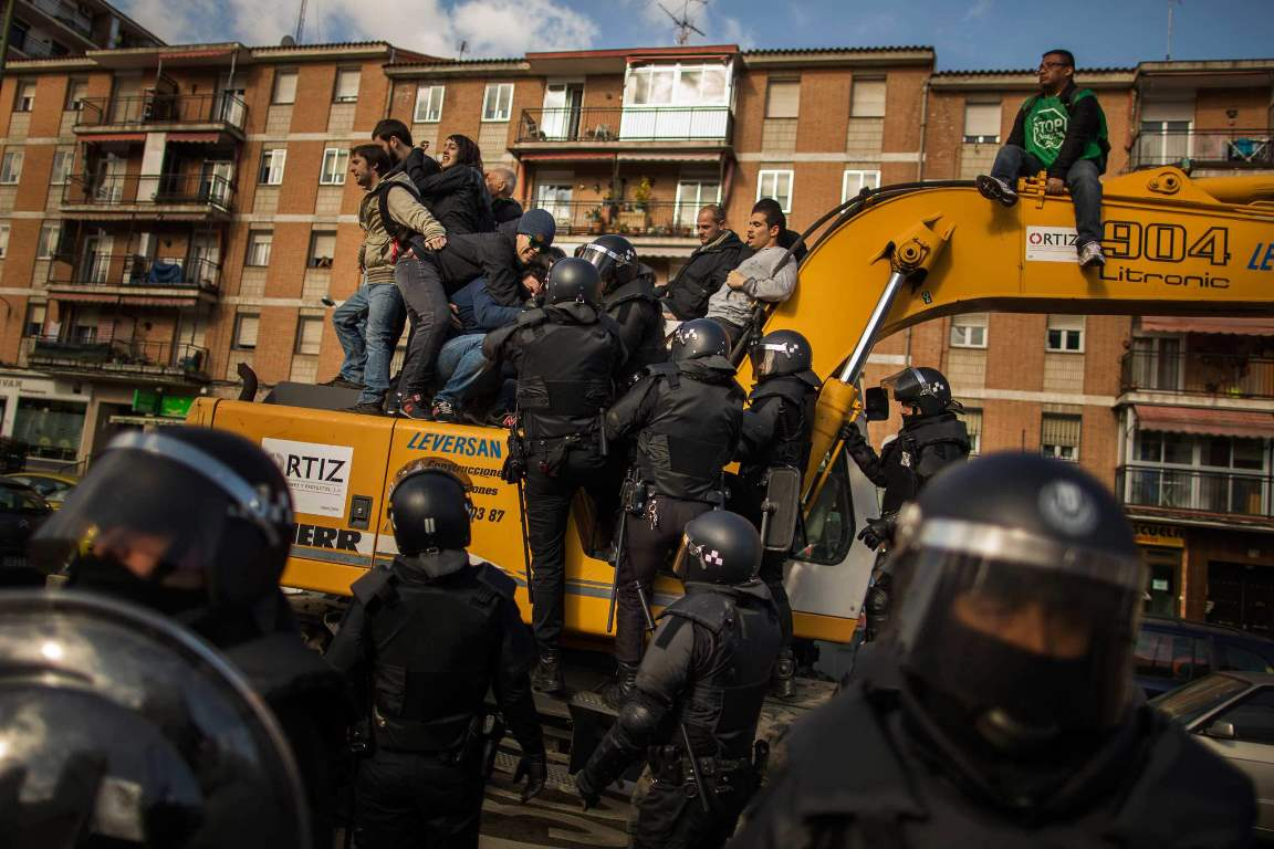 Riot Police remove a housing rights activists who claimed a bulldozer as they triy to stop Luisa Gracia Gonzalez and her family's eviction and the demolition of their house by a forced expropriation in Madrid, Spain, Friday, Feb. 27, 2015. Madrid authorities say 11 people were arrested after several dozen protesters clashed with police who were carrying out an eviction order. A city spokeswoman said seven people were arrested for throwing gasoline at police officers, though she said the fuel was not set alight. The official spoke on condition of anonymity in keeping with city hall rules. Evictions in Spain have soared since the country's economic crisis began in 2008 and increasing numbers of people were unable to meet mortgage payments. Protesters regularly try to prevent evictions, but Friday's clash was particularly tense after a campaign to keep the family in its home. The house was expropriated for demolition as part of new urban project. Some 30 protesters tried to stop it, accusing authorities of real estate speculation. (AP Photo/Andres Kudacki)