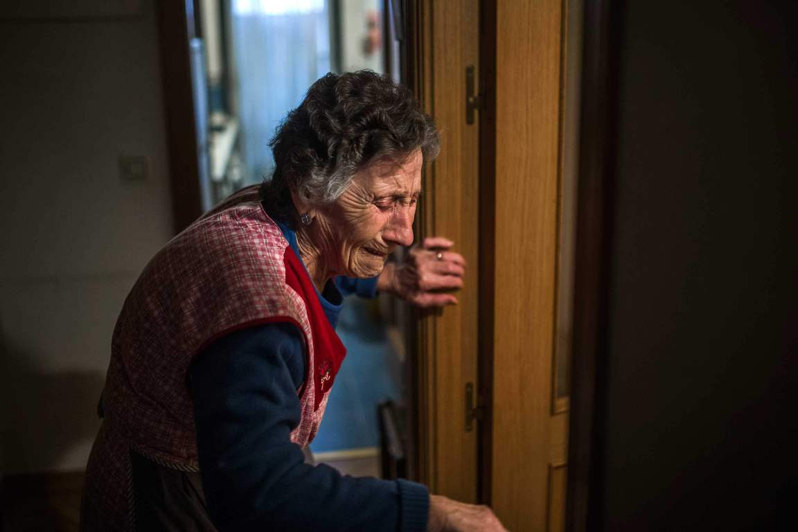 Carmen Martinez Ayudo, 85-years old, cries during her eviction in Madrid, Spain, Friday, Nov. 21, 2014. Carmen Martinez Ayudo lost her foreclosed apartment to a moneylender after she could not afford to pay her debt and the high interest rates due to her financial situation after his son lost his job. Martinez Ayudo got evicted inspite of housing right activists clash with the dozens of riot police and at least one protestor was arrested. (AP Photo/Andres Kudacki)