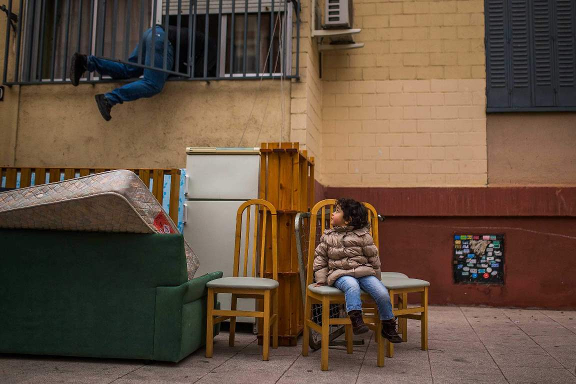 In this picture taken Wednesday, Feb. 11, 2015, Diana Sofia Meliton, 2 years old, sits outside together with belongings after her and her family got evicted by the police and watches a housing right activist re-opening her apartment for them to live in Madrid, Spain. Pablo Enrique Meliton, 39 years old, his wife Damaris Varela Rivera, 36 yeas old , and their daughter Diana Sofia Meliton, 2 years old, rent a room in a occupied Bankia bank apartment one year ago as they could not afford to pay rent and stay occupying the apartment after the rest of the occupants left. They have now an income of euro 790 ($893) and they have tried to negotiate to pay a low rent but the Bankia bank demanded their eviction. Housing right activists tried to stop the process but the police evicted the family. (AP Photo/Andres Kudacki)