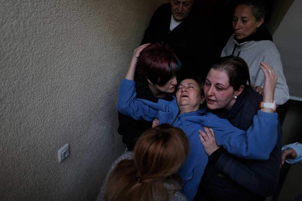 Soledad Carrasquilla Delgado, 53 years old, centre, gets help from her daughter, centre right, her sister, centre left, her husband, top left, and two members of the Victims' Mortgage Platform (PAH), top right, and bottom, as she faints during a panic attack following the postponement of her and her family's eviction in Madrid, Spain, Wednesday, Oct. 30, 2013. Carrasquilla Delgado and her husband Cecilio Escudero Hidalgo, 53 years old, live with their son Aitor, 21 years old, and their daughter Noelia, 28 years old, in an apartment of the Madrid Housing Institute (IVIMA) for seventeen years. They are all unemployed and the family's income are state benefits of 426 euros ($586) and 564 euros ($776). IVIMA offered them to buy the property but they could not afford it. The eviction was finally postponed with the help of the Victims' Mortgage Platform (PAH). (AP Photo/Andres Kudacki)