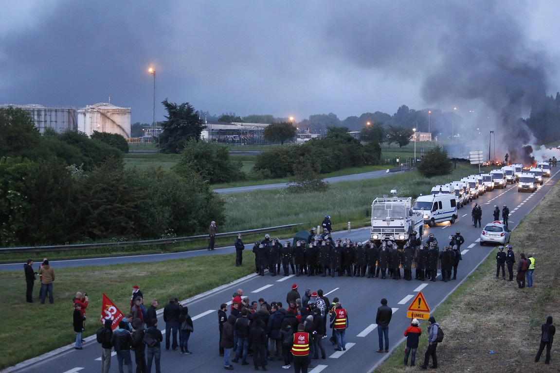 epa05327822 French police dislodge protesters blocking a fuel depot after trade unionists erected a burning barricade to block the entrance of a refinery in Douchy-les-Mines, northern France, early 25 May 2016. A strike hit oil refineries, fuel depots and petrol stations across France. EPA/THIBAULT VANDERMERSCH