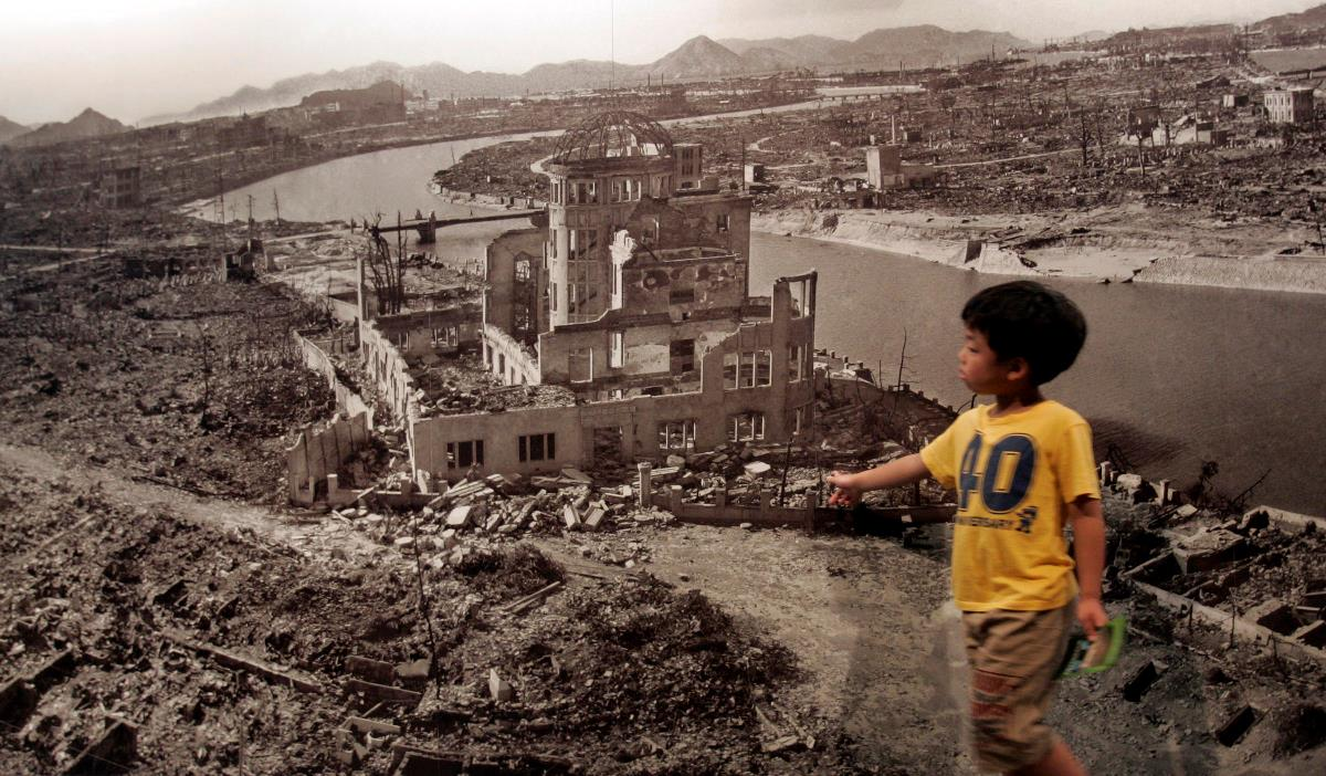 A boy looks at a huge photograph showing Hiroshima city after the 1945 atomic bombing, at the Hiroshima Peace Memorial Museum, Japan August 6, 2007. Japan marked the 62nd anniversary of Hiroshima's atomic bombing with a solemn ceremony on Monday as the city's mayor criticised the United States for refusing to give up its nuclear weapons programme. REUTERS/Toru Hanai (JAPAN) - RTR1SJY9